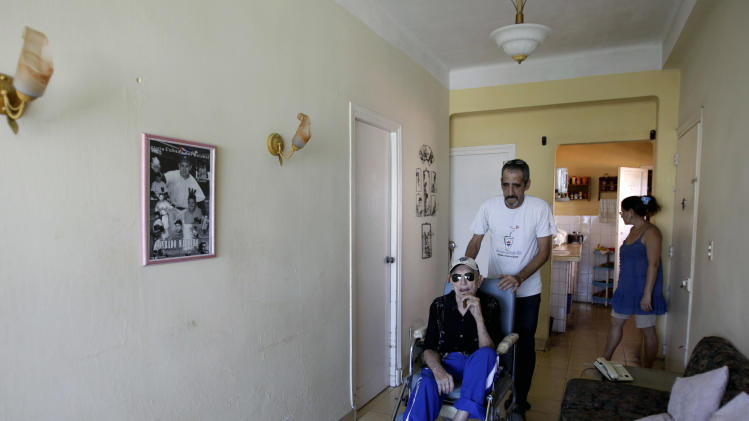 In this April 23, 2013 photo, Conrado Marrero, the world's oldest living former major league baseball player, is pushed in a wheelchair by his grandson Rogelio Marrero at their home two days before is 102nd birthday in Havana, Cuba. In addition to his longevity, the former Washington Senator has much to celebrate this year. After a long wait, he finally received a $20,000 payout from Major League baseball granted to old-timers who played between 1947 and 1979. The money had been held up since 2011 due to issues surrounding the 51-year-old U.S. embargo on Cuba, which prohibits most bank transfers to the Communist-run island. But the payout finally arrived in two parts, one at the end of last year, and the second a few months ago, according to Marrero's family. (AP Photo/Franklin Reyes)