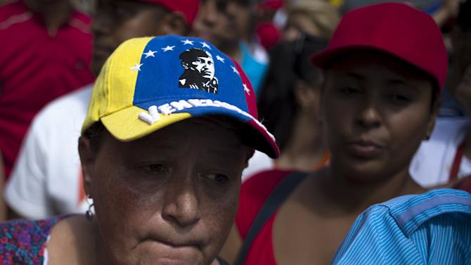 A woman wears a cap bearing the image of the late Venezuelan President Hugo Chavez during a rally outside Miraflores Palace in Caracas, Venezuela