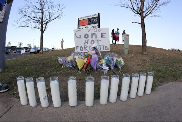 Candles and a sign stand for victims of a mass shooting across from the site at the Century 16 theatre east of the Aurora Mall in Aurora, Colo., on Friday, July 20, 2012. Authorities report that 12 di