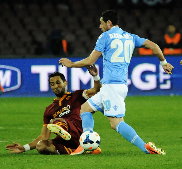 Napoli's Blerim Demaili, right, is tackled by AS Roma's Mehdi Benatia during a Serie A soccer match between Napoli and Roma, at the San Paolo stadium in Naples, Italy, Sunday, March 9, 2014