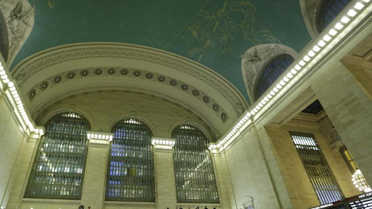 A woman looks up from the main concourse at the celestial display painted on the ceiling inside Grand Central Terminal in New York, Tuesday, Jan. 8, 2013.  The country's most famous train station and one of the finest examples of Beaux Arts architecture in America turns 100 on Feb. 1. The building's centennial comes 15 years after a triiumphant renovation that removed decades of grime and decay and restored it's glittering chandeliers, cathedral windows and the celestial ceiling. (AP Photo/Kathy Willens)
