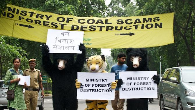 Greenpeace activists hold placards during a protest, urging the government to stop using the corruption-induced coal shortage as an alleged reason to mine in forest areas, outside the Coal Ministry in New Delhi on September 11, 2012
