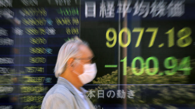 A man walks in front of the electronic stock board of a securities firm as Japan's Nikkei 225 index falls 100.94 points to 9077.18 in Tokyo Friday, Aug. 24, 2012. Asian markets fell Friday as disappointment over weak economic indicators from the United States, China and Europe offset hopes for more stimulus from central banks. (AP Photo/Itsuo Inouye)