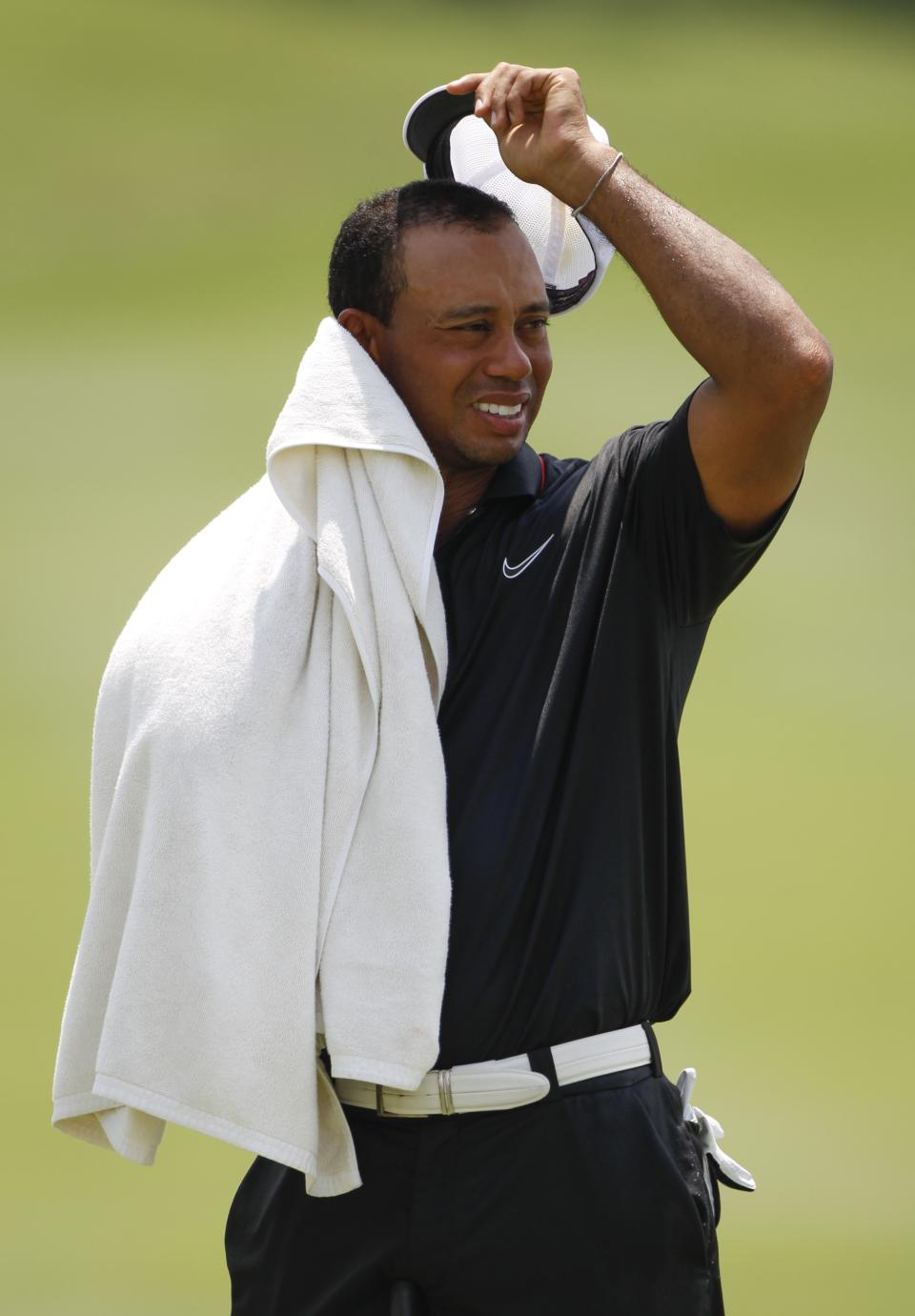Tiger Woods of the United States wipes his face down with a towel on the 11th hole during the round two of CIMB Classic golf tournament at the Mines Resort and Golf Club in Kuala Lumpur, Malaysia, Friday, Oct. 26, 2012.  (AP Photo/Vincent Thian)