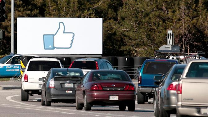 Cars are shown driving past a sign at Facebook headquarters in Menlo Park, Calif., Thursday, Feb. 23, 2012. As hundreds of employees at Facebook's new headquarters wonder how to spend their millions when the company goes public, the city just up the road has different problems. (AP Photo/Jeff Chiu)