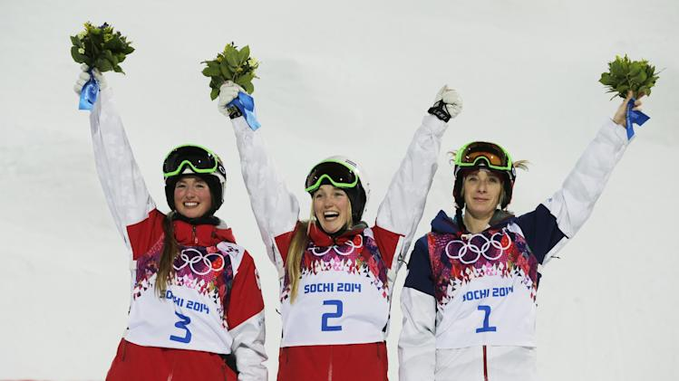 Canada's Justine Dufour-Lapointe, center, celebrates her gold medal in the women's moguls final, with her sister and silver medalist Chloe Dufour-Lapointe, left, and bronze medalist United States' Hannah Kearney, at the Rosa Khutor Extreme Park, at the 2014 Winter Olympics, Saturday, Feb. 8, 2014, in Krasnaya Polyana, Russia