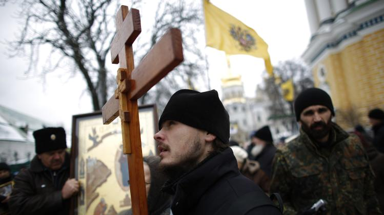 A believer holds a wooden cross during a procession of relics and pictures of Eastern Orthodox saints commemorating the icon of St. Nicholas the Drenched, in Kiev