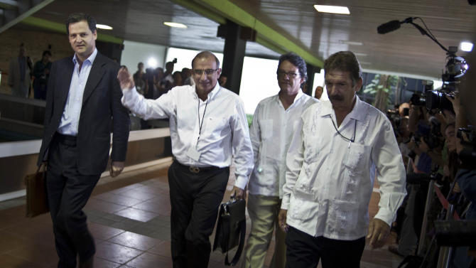 Humberto de la Calle, second from left, head of Colombia's government peace negotiation team, is accompanied by Sergio Jaramillo, left, and Gustavo Adolfo Bell Lemus, second from right, as they are escorted by a Cuban security official, right, to peace talks in Havana, Cuba, Monday, Nov. 19, 2012. Cuba is playing host to the talks in Havana following an initial round of discussions in Oslo, Norway between the Revolutionary Armed Forces of Colombia, or FARC, and Colombian government.  The FARC has been at war with the Colombian government for nearly half a century. (AP Photo/Ramon Espinosa)