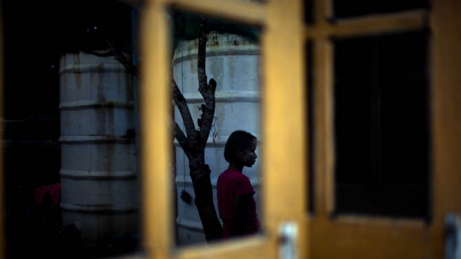 """In this Aug. 29, 2012 photo, reflected in a window, a six-year-old girl Myat Noe Thu, with Burmese local sunscreen """"Thanakha"""" applied on her face, stands at a courtyard alone while her HIV-infected parents and younger sister, unseen in the photo, rest in a hut at an HIV/AIDS center on the outskirts of Yangon, Myanmar. Myat is not infected with HIV. Following a half century of military rule, care for HIV/AIDS patients in Myanmar lags behind other countries. Half of the estimated 240,000 people living with the disease are going without treatment and 18,000 are dying from it every year. (AP Photo/Alexander F. Yuan)"""