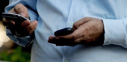 "A man sends a text message on his mobile phone. A Gulf rights group and a Kuwaiti MP have criticised the arrest of a member of the Gulf state's ruling family for expressing ""political views"" deemed offensive"