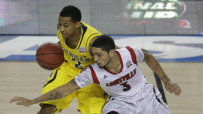 Louisville guard Peyton Siva (3) and Michigan guard Trey Burke (3) work during the second half of the NCAA Final Four tournament college basketball championship game Monday, April 8, 2013, in Atlanta. (AP Photo/Chris O'Meara)