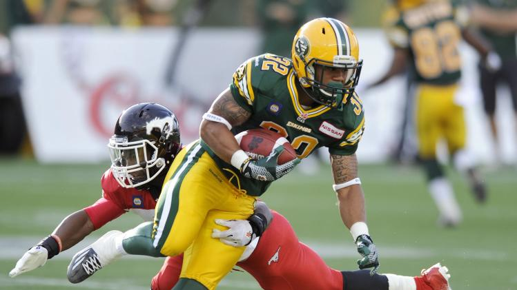 Eskimos' Lawrence gets by Stampeders' Smith during their CFL football game in Edmonton