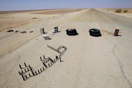 An abandoned check point on the road between Garyat and Shwayrif, 400 kms south of Tripoli in the south desert of Libya, Thursday, Sept. 15, 2011. (AP Photo/Francois Mori)