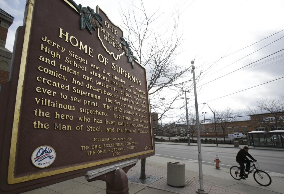 In this Tuesday, April 2, 2013 photo shows a man riding his bicycle past the Home of Superman plaque in Cleveland. Superman collaborators Jerry Siegel and Shuster lived several blocks apart in the Glenville neighborhood which shaped their lives, dreams for the future and their imagery of the Man of Steel. (AP Photo/Tony Dejak)