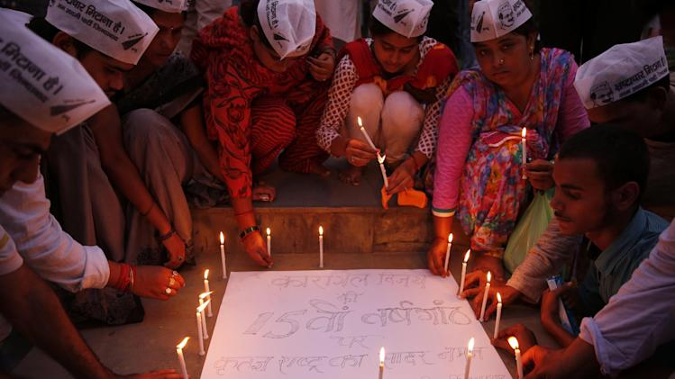 "Indian activists of the Aam Aadmi Party, or Common Man Party, light candles during an event to mark the 15th anniversary of India's victory in the Kargil War, in Allahabad, India, Saturday, July 26, 2014. The 1999 conflict with Pakistan raged for three months across the disputed Kashmir region and nearly brought the nuclear neighbors to a war. The poster reads ""On the 15th anniversary of the Kargil War, a grateful nation bows down to you."" (AP Photo/ Rajesh Kumar Singh)"