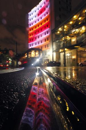 A hotel is reflected in puddles of rain from approaching Tropical Storm Lee at a streetcar track, as a streetcar passes through Lee Circle, in New Orleans, Friday, Sept. 2, 2011. Lee formed in the waters off Louisiana on Friday, threatening a drenching along much of the Gulf coast over the Labor Day weekend with up to 20 inches (50 centimeters) of rain in some spots. (AP Photo/Gerald Herbert)