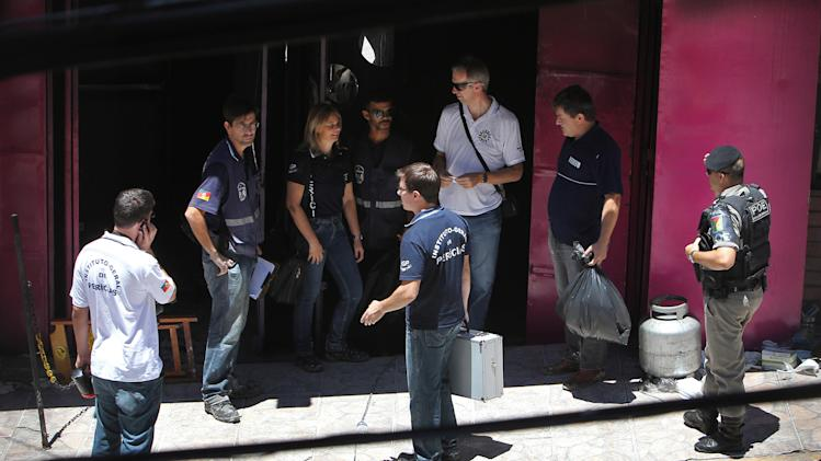 Police investigators work at the entrance of the Kiss nightclub where a fatal fire broke out in Santa Maria, Brazil, Monday, Jan. 28, 2013.  A fast-moving fire roared through the crowded, windowless Kiss nightclub in this southern Brazilian city early Sunday, killing more than 230 people. Many of the victims were under 20 years old, including some minors. (AP Photo/Nabor Goulart)