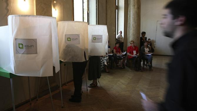 Georgians vote during Parliamentary elections at a polling station in Tbilisi, Georgia, Monday, Oct. 1, 2012. Voters in Georgia are choosing a new parliament in a heated election Monday that will decide the future of Saakashvili's government. (AP Photo/Shakh Aivazov)