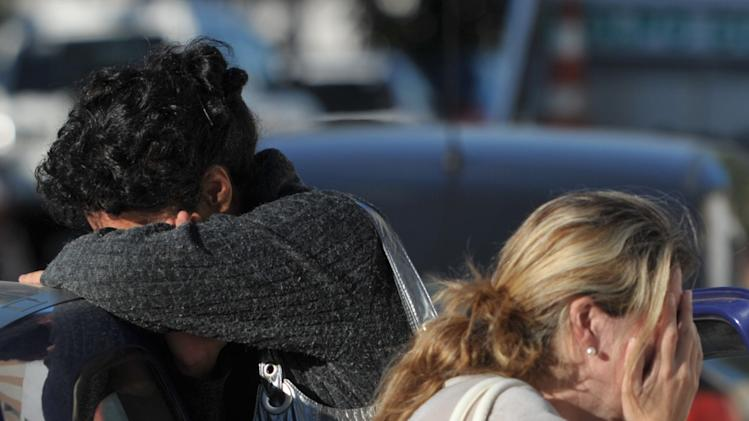 ALTERNATIVE CROP OF XSI108.- Relatives of victims react as they wait for news near the Kiss nightclub in Santa Maria city,  Rio Grande do Sul state, Brazil, Sunday, Jan. 27, 2013.  According to police more than 200 died in the devastating nightclub fire in southern Brazil.  Officials say the fire broke out at the club while a band was performing. (AP Photo/Ronald Mendes-Agencia RBS)