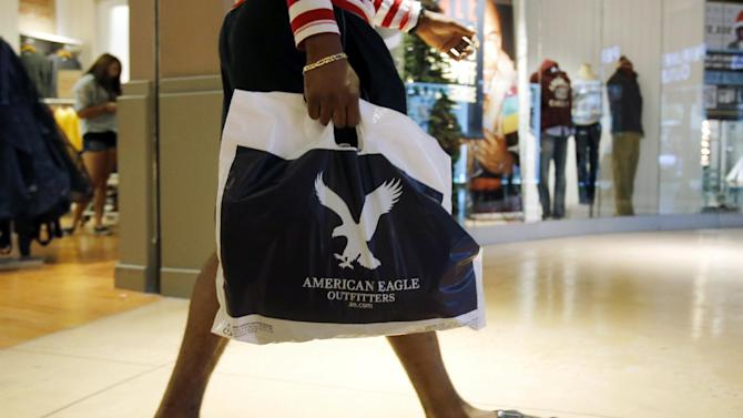 In this Thursday, Dec. 20, 2012 photo, a shopper carries a bag at the Dolphin Mall in Miami. A last-minute surge in spending helped many major U.S. retailers report better-than-expected sales in December, a relief for stores that make up to 40 percent of annual revenue during the holiday period. (AP Photo/Alan Diaz)