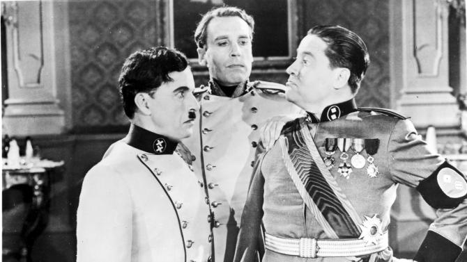 "FILE--This file photo provided by Columbia Pictures shows a confrontation between The Great dictator, Charlie Chaplin, left, and Jack Oakie, dictator of bacteria, right, in a scene from the classic film satire on Nazi Germany, ""The Great Dictator,"" from 1940. Henry Daniell as Garbitsch looks on. (AP Photo/Columbia Pictures, File)"