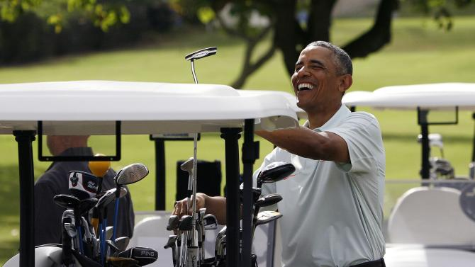 U.S. President Barack Obama puts his putter in the bag after he and Malaysia's Prime Minister Najib Razak played on the 18th green in Kaneohe
