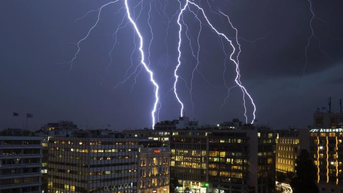 Lightning strikes over buildings at central Syntagma square during heavy rainfall in Athens