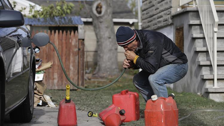 Chris Zaturoski uses a garden hose to attempt to siphon gasoline from his car to use in a generator at his house which is without power in the wake of superstorm Sandy on Thursday, Nov. 1, 2012, in Little Ferry, N.J. The price of oil is rising as operations at refineries and supply terminals in the Northeast remain restricted three days after Superstorm Sandy. Benchmark oil gained 60 cents Thursday to $86.84 per barrel in New York.  (AP Photo/Mike Groll)