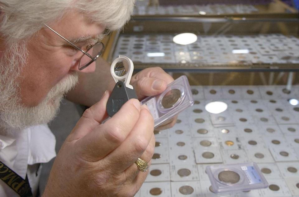 "John Edgar of Knoxville, Tennessee looks at ""must have"" rare coins at the booth of Eugene Bruder of Chico, California during the National Money Show held by the American Numismatic Association in the New Orleans Convention Center in New Orleans, La., Thursday, May 9, 2013. (AP Photo/Matthew Hinton)"