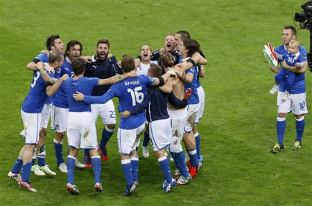 Italy's Cassano with baby in his hands looks on team mates as they celebrate their victory against Germany at Euro 2012 semi-final soccer match at the National stadium in Warsaw