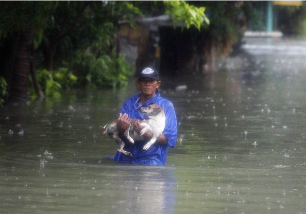 2012-08-07T031842Z_798911754_GM2E8870VBE01_RTRMADP_3_PHILIPPINES-FLOODS - A man carries his pet dog as he wades on a flooded street - Philippine Photo Gallery