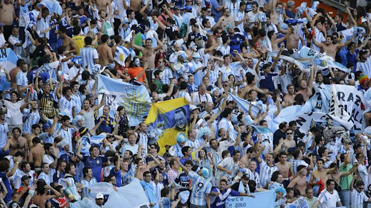 Argentine fans celebrate after Lionel Messi scored during the group F World Cup soccer match between Argentina and Iran at the Mineirao Stadium in Belo Horizonte, Brazil, Saturday, June 21, 2014. Lionel Messi scored a superb goal in stoppage time to give Argentina a 1-0 victory over Iran