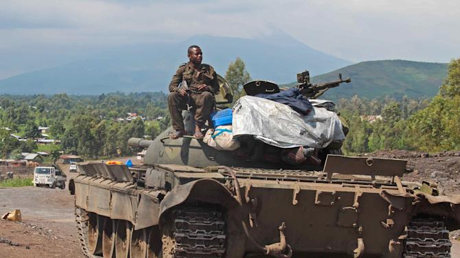 A Congolese army tank overlooking Munigi and the road to Rutshuru where fighting between the M23 and the Congolese army has been taking place in the past days near Goma, Congo, Monday, Nov. 19, 2012. Rebels believed to be backed by Rwanda fired mortars and machine guns Monday in a village on the outskirts of the provincial capital of Goma and threatened to attack the city which is protected by ragtag Congolese government troops backed by United Nations peacekeepers. The gunfire and explosions erupted in the early afternoon, hours after the M23 rebels said they were halting fighting in order to negotiate with the government of Congo. (AP Photo/Melanie Gouby)