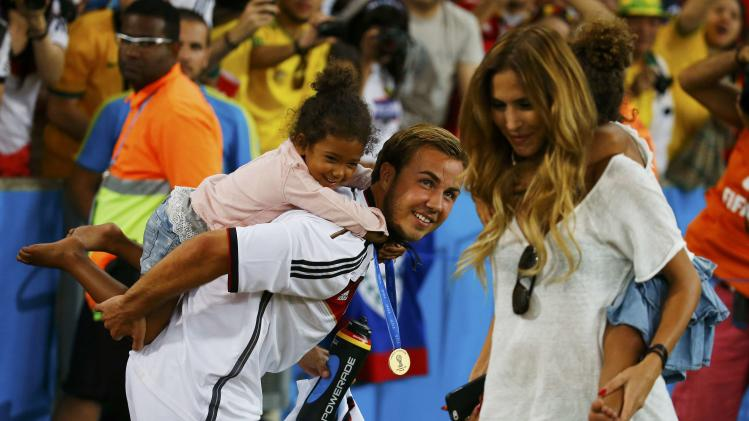 Germany's Goetze and his girlfriend Brommel carry twin daughters of Boateng at the end of during their 2014 World Cup final against Argentina at the Maracana stadium in Rio de Janeiro