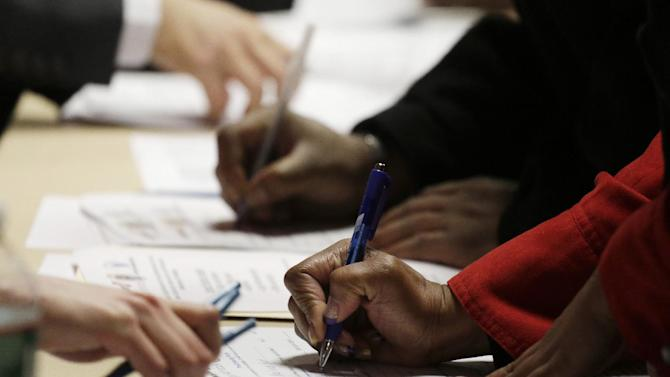 In this Wednesday, Feb. 6, 2013, photo, job applicants complete forms at a job fair sponsored by Swissport, in Newark N.J. The number of Americans seeking unemployment aid fell 22,000 last week to a seasonally adjusted 344,000, evidence that the job market may be picking up. (AP Photo/Mark Lennihan)