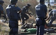 FILE - In this file photo taken Thursday, Aug. 16, 2012 police surround the bodies of striking miners after opening fire on a crowd at the Lonmin Platinum Mine near Rustenburg, South Africa. A government commission investigating the shooting deaths of 34 striking miners by South African police at the Marikana mine says the police force has lied, withheld documents and apparently doctored other papers. (AP Photo-file)