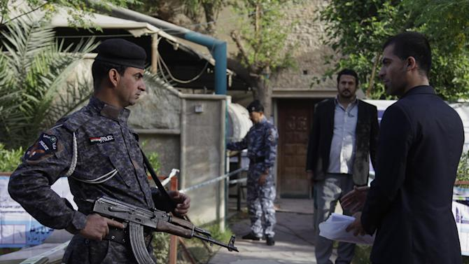 An Iraqi soldier stands guard as Iraqi people prepare to cast their ballots at a polling center during the country's provincial elections in Baghdad, Iraq, Saturday, April 20, 2013. (AP Photo/ Khalid Mohammed)