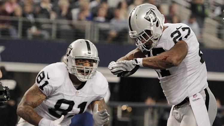 Oakland Raiders running back Rashad Jennings (27) celebrates his touchdown against the Dallas Cowboys with Mychal Rivera during the first half of an NFL football game, Thursday, Nov. 28, 2013, in Arlington, Texas