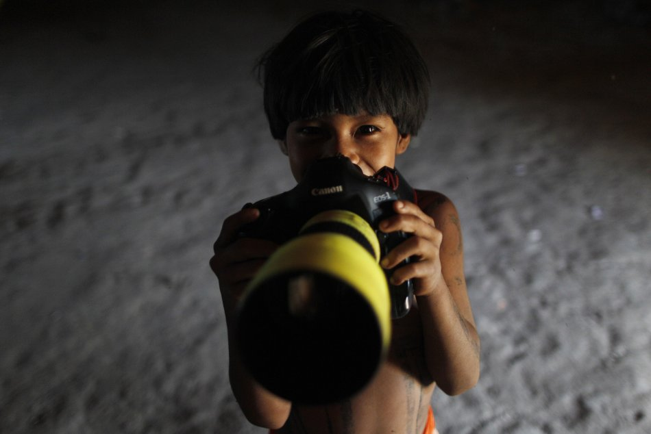 A Yawalapiti boy poses with a camera in the Xingu National Park