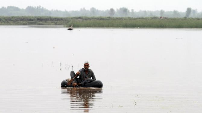 A man crosses floodwater on a handmade raft at Camp Koruna Akbar in the Pura area of  Nowshera district