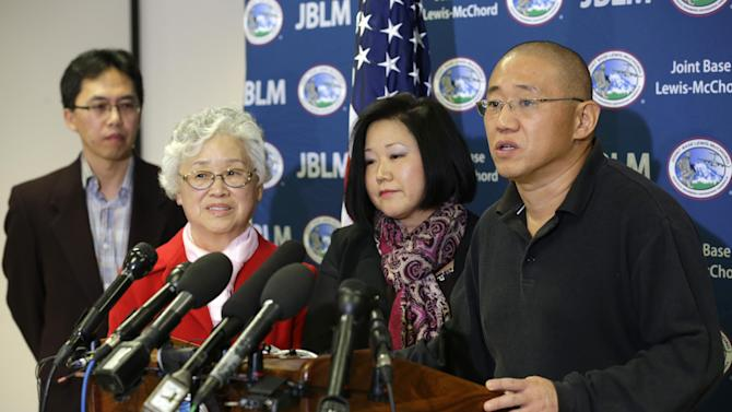 Kenneth Bae, right, who had been held in North Korea since 2012, talks to reporters after he arrived Saturday, Nov. 8, 2014, at Joint Base Lewis-McChord, Wash., after he was freed during a top-secret mission. Looking on from left are Bae's brother-in-law Andrew Chung, his mother, Myunghee Bae, and his sister, Terri Chung. (AP Photo/Ted S. Warren)