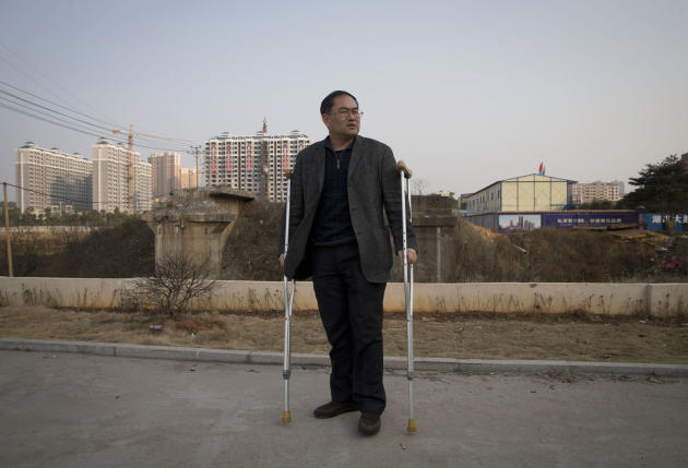 In this Monday, Jan. 20, 2014 photo, Zhou Wangyan, head of the Liling city land resources bureau, stands with crutches near a plot of land under development in Liling city in central China's Hunan