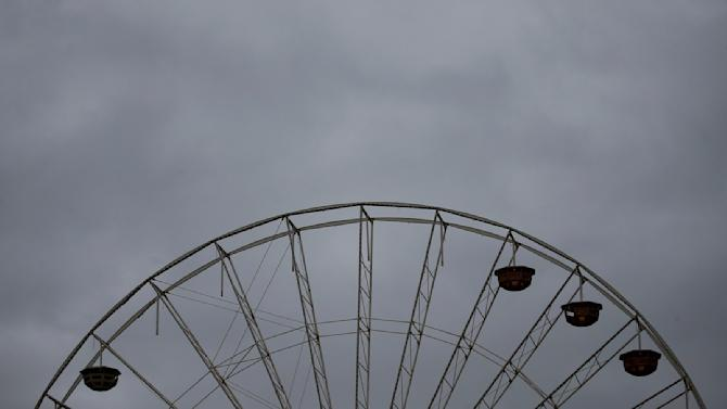 Partially dismantled carnival ferris wheel is silhouetted against a stormy sky during Rosenmontag in Mainz
