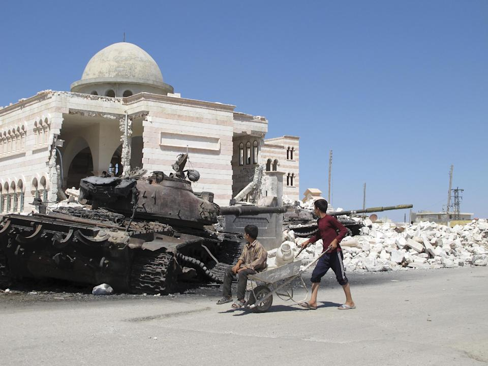 Syrian boys fetching water in a wheelbarrow look at a destroyed Syrian tank near a damaged mosque in the city of Azaz, Syria, on Monday, Aug. 20, 2012. (AP Photo/Ben Hubbard)
