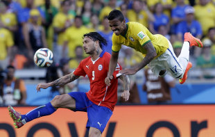 Chile's Mauricio Pinilla, left, and Brazil's Luiz Gustavo battle for the ball during match between Brazil and Chile. (Andre Penner/AP Photo)
