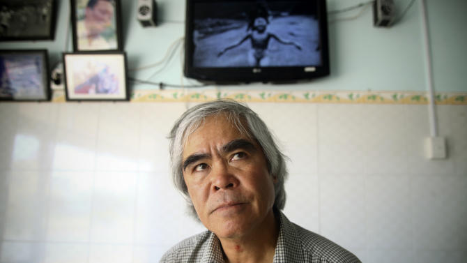 "In this March 29, 2012 photo, Associated Press photographer Huynh Cong ""Nick"" Ut visits Kim Phuc's house near the place he took his famous Pulitzer Prize winning photograph of her as a terrified 9-year-old in Trang Bang, Tay Ninh province, Vietnam. The iconic black-and-white image of the aftermath of a napalm attack communicated the horrors of the Vietnam War in a way words could never describe and contributed to its end. But behind the camera, it also brought the wounded girl together with the young photographer, and it came to define her life both as a curse and ultimately as a savior. (AP Photo/Na Son Nguyen)"