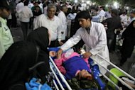 An Iranian medic attends to an injured woman as people gather outside a hospital in the town of Ahar, some 60 kms east of Tabriz, after a strong earthquake hit northwestern Iran
