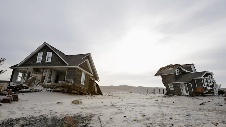 FILE - This Feb. 22,2013 file photo shows Two heavily damaged homes on the beach in Mantoloking, N.J., from Superstorm Sandy. Man-made global warming may decrease the likelihood of the already unusual steering currents that pushed Superstorm Sandy due west into New Jersey in a freak 1-in-700 year path, researchers report. While that may sound like the rare good climate change news, it's probably not, according to the study's authors, because they only looked at steering currents and other factors, including stronger storms, and sea level rise can and likely will outweigh any benefit from changing air patterns. The study is disputed by other scientists who have been vocal about the meteorological factors behind Sandy. (AP Photo/Mel Evans, File)