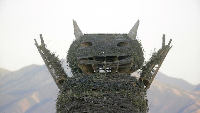 """This Saturday July 12, 2014, photo, shows the upper portion of a giant wooden effigy of a character from the classic children's book, """"Where the Wild Things Are,"""" before it was burnt Saturday night, during the Element 11 festival, an event similar to Burning Man, in Grantsville, Utah, about 36 miles southwest of Salt Lake City. Police say Salt Lake City resident Christopher Wallace died after jumping into the burning three-story-tall effigy effigy. (AP Photo/Rick Bowmer)"""