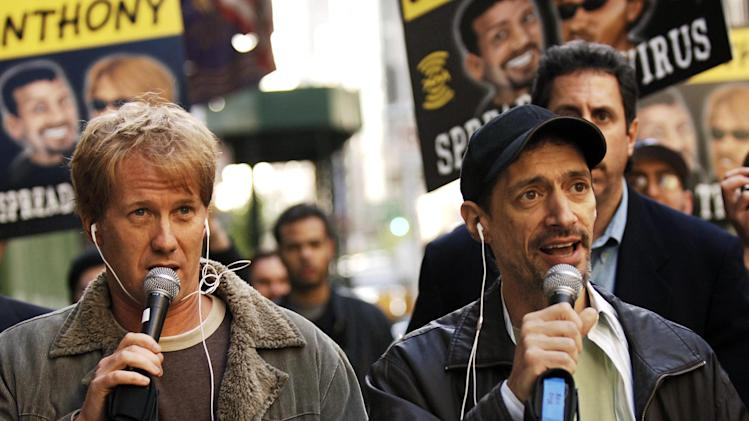 "FILE - In a April 26, 2006 file photo, radio shock jocks Greg ""Opie"" Hughes, left, and Anthony Cumia, right, leave CBS Radio studios on 57th Street with fans after finishing their first morning show, in New York. Cumia is offering no apologies for what satellite radio company SiriusXM called a hate-filled Twitter rant that got him fired. The former co-host of the ""Opie and Anthony Show"" was let go on July 3 after tweeting his outrage at a woman he said punched him in the face on a New York street. Cumia responded in an interview early Saturday, July 12, 2014, on Fox News' ""Red Eye."" His tweets used an expletive degrading to women, and SiriusXM called them ""racially charged."" The woman he encountered is black. (AP Photo/ Louis Lanzano, File)"